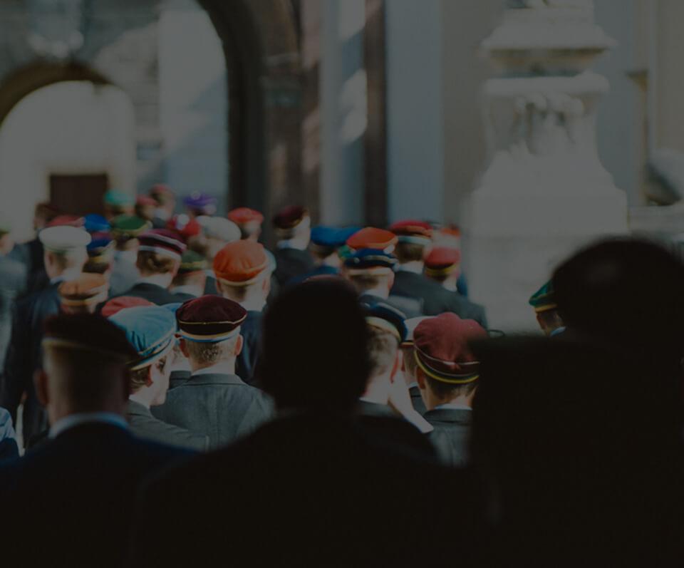 Dekorative Grafik: Eine Gruppe von katholischen Verbindungstudenten, aufgenommen von hinten im Kreuzgang einer Kirche.