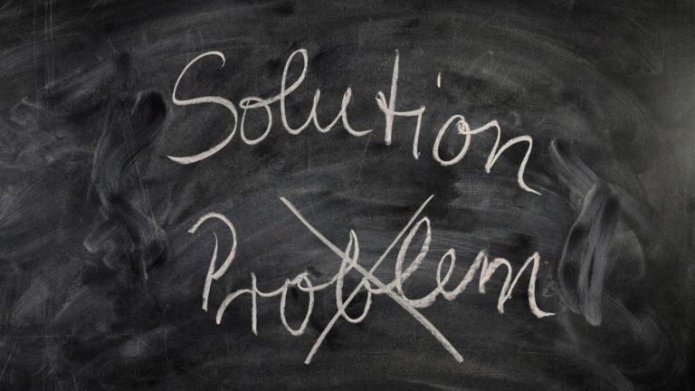 Dekorative Grafik: Grüne Schultafel beschriftet mit weißer Kreide. Das Wort Problem ist durchgestrichen, darüber das englische Wort Solution, auf deutsch: Lösung.