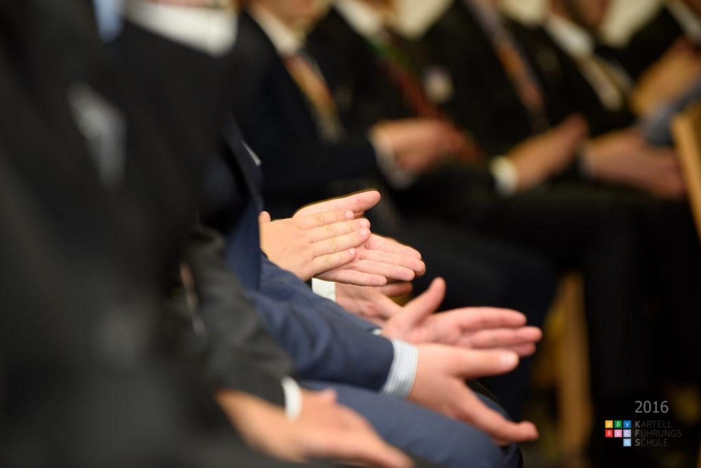 Dekoratife Grafik: Personen sitzend im Halbkreis klatschen. Der Fokus des Bildes liegt auf den Händen der ersten drei Personen im Halbkreis. Die Gesichter sind nicht zu erkennen.