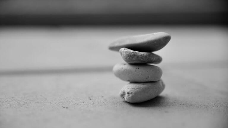 Dekorative Grafik: Vier Steine die übereinander gestapelt stehen. Die Steine sind der Form nach Kieselsteine, jedenfalls aber mit abgerundeten Kanten.