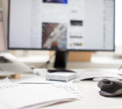 Dekorative Grafik: Ein Schreibtisch, im Vordergrund ist ein Notizheft zu sehen. Daneben liegt eine Computermaus. Im Hintergrund, unscharf zu sehen sind ein Laptop und ein externer Bildschirm. Zusätzlich sind noch ein Becher und ein Stift im Hintergrund zu erkennen.