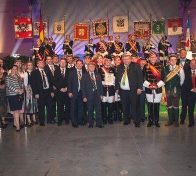 Gruppenfote anlässlich der Verleihung des Sozialpreises. Mitglieder der Verbindung Vindobona 2 nehmen in vor den Standarten der Landesverbände des MKV entgegen.