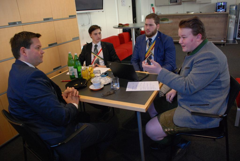 Interview mit Lukas Mandl. Sitzend am Tisch mit drei Interviewern im Gespräch
